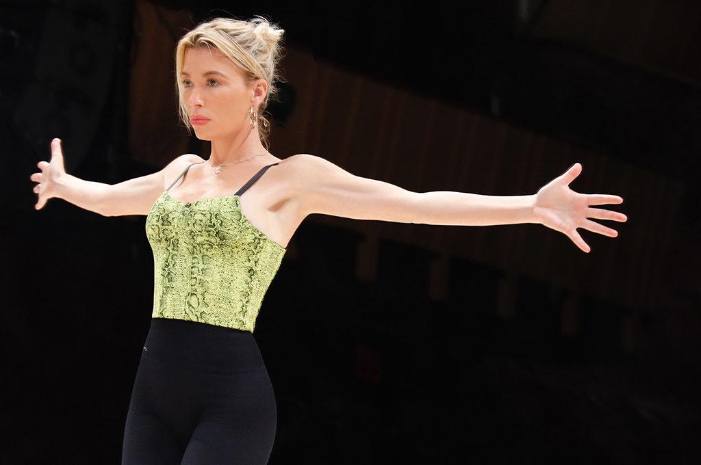 Tracy Anderson tanzend mit schwarzer leggings und gelb grünem Oberteil