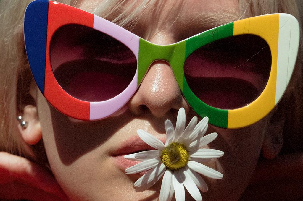 close-up Frau mit bunter Sonnenbrille und Blume im Mund