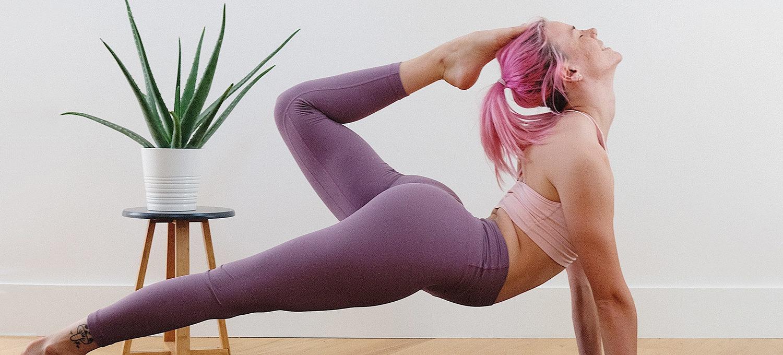 Frau mit pinken haaren im Bett scorpion fortgeschrittene yoga pose