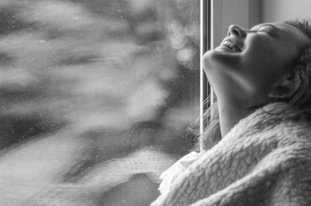 Frau in schwarz weiss sitzt mit einer dicken decke im Fenster rahmen und lacht