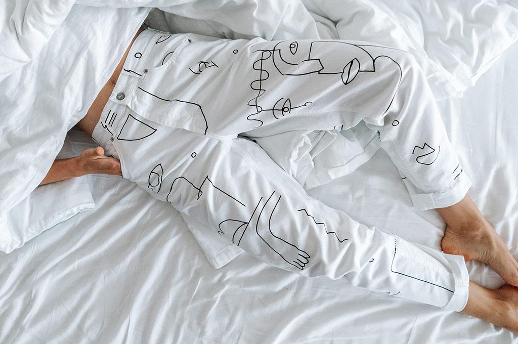 Beine einer Frau mit weisser hose in einem weissen Bett