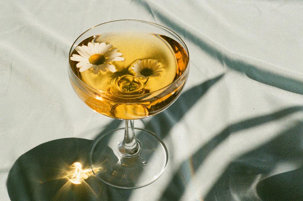 ein drink mit einer Blume im glas steht auf einem Türkisen Stoff