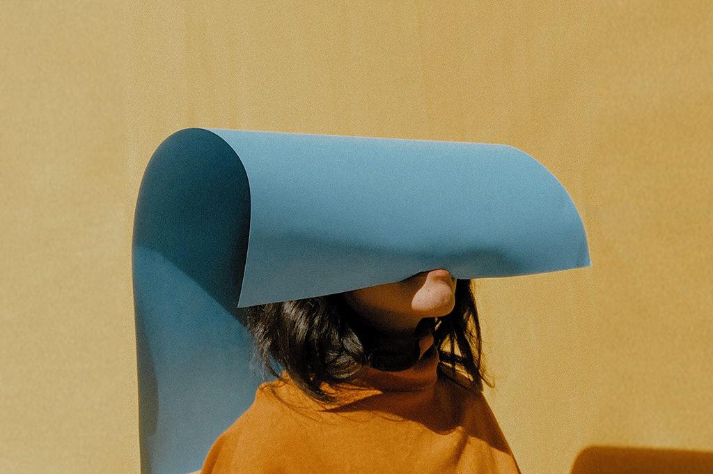 Frau vor gelber wand hat eine blaue Pappe im Mund die ihr über en kopf fällt