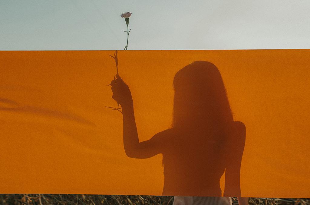Silhouette einer Frau hinter einem orangen Leintuch. Sie hält eine Blume in der Hand welche oben heraus schaut.