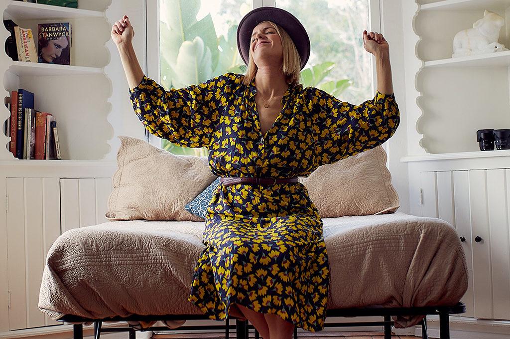 Frau sitzt zuhause mit Hut auf einem Sofa und freut sich