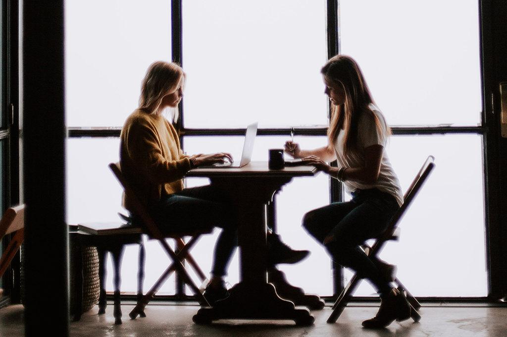 zwei Frauen sitzen sich in einem Loft an einem Tisch gegenüber und arbeiten. Gegenlicht durch das Fenster vor dem sie sitzen.