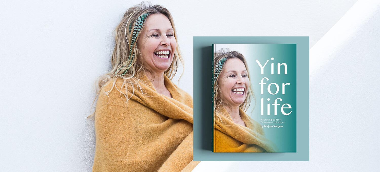 Mirjam Wagner steht lachend an eine Wand gelehnt. daneben Buch von ihr Yin for Life