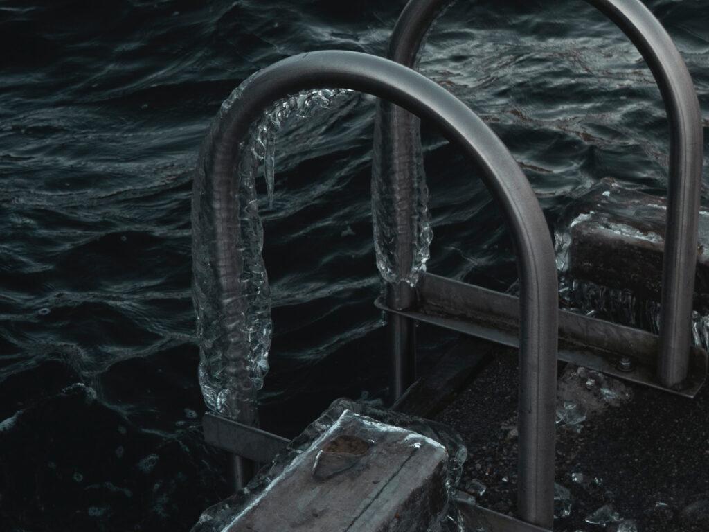 ein eingefrorenes Geländer das ins Wasser führt