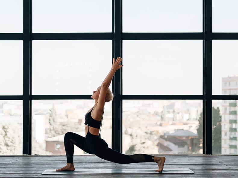 Frau vor einem großen Fenster in einer High Lunge Position