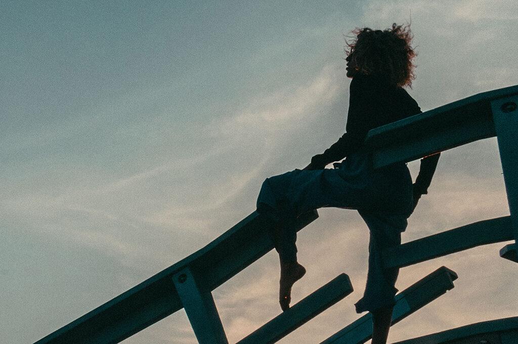 Frau sitzt in Sonnenuntergangs-Stimmung auf einem Geländer