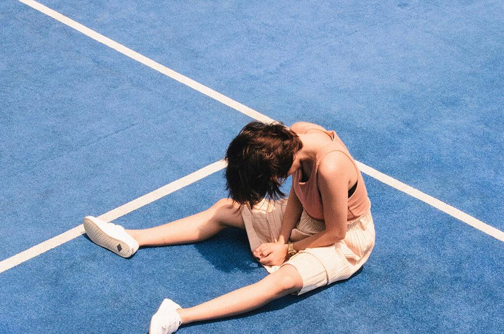 Frau sitzt auf einem blauen Tennis Court