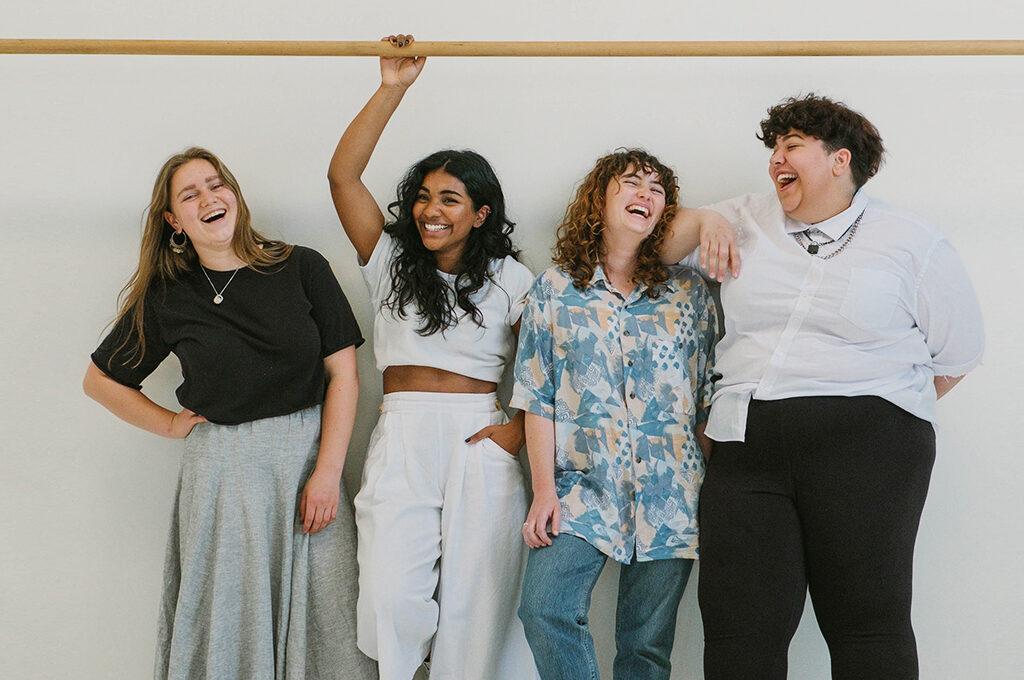 4 Frauen mit unterschiedlichen Hautfarben und Kleidergrößen stehen lachend vor eine weißen Wand