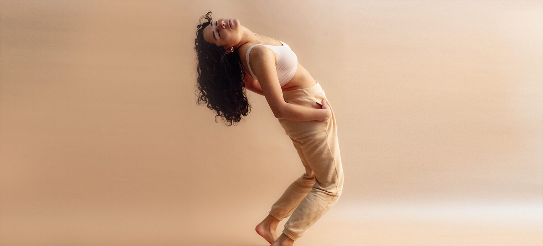 eine Frau steht in beider Jogginghose und BBustier vor einem beigen Hintergrund. Sie lässt den Kopf und ihre dunklen langen Haaren nach hinten fallen.