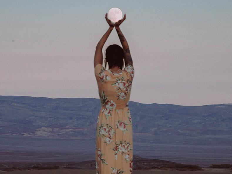 Ein Frau hält den Mond in ihren Händen