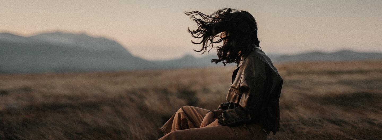 eine Frau sitzt in der Natur und der Wind weht ihr Haar von hinten nach vorne