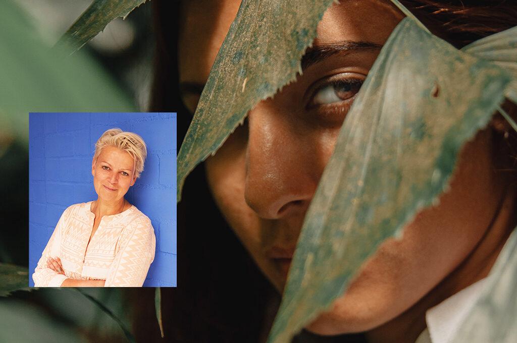 im Hintergrund ein Frauen Gesicht versteckt hinter Blättern.Bild von Marion Müller.